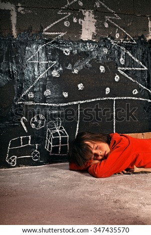 Poor boy sleeping on the street dreaming of christmas presents - stock photo