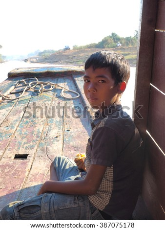 poor cambodian boy working on a boat in floating village