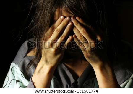 Poor dirty girl crying with hands on her face - stock photo