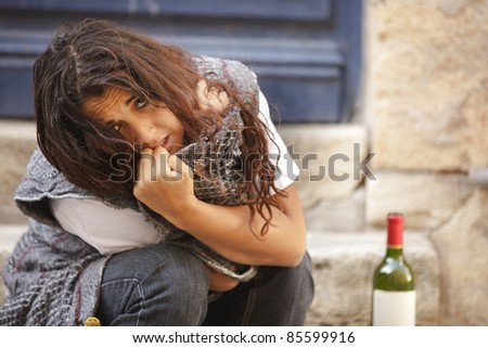 poor drunk woman sitting on sidewalk with bottle of wine - stock photo