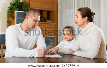 Poor family counting money to pay bills at the table at home - stock photo