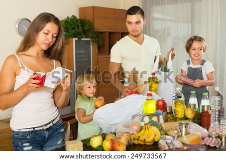 Poor family of four with bags of food at home. Focus on woman