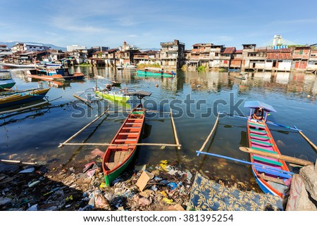 poor houses with sheet tin by the river with boats on the river,Kota Manado, North Sulawesi, Indonesia - stock photo