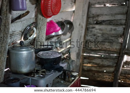 Poor kitchen in the house of worn wooden planks. The kitchen contains only the most necessary equipment like pots, plates, bowls and glasses. Wretched rickety hovel - stock photo