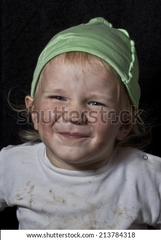 poor laughing messy child on black background - stock photo