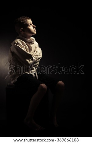 Poor Lonely Young Boy Sitting on a Chair in an Isolation Room, Looking Up While Hugging Himself in a Pensive Facial Expression. - stock photo