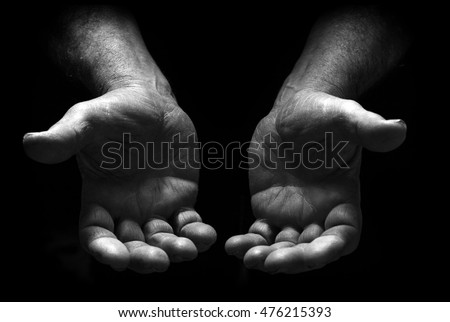 Poor man begging with outstretched hands. Hands forming a cup. Poverty and marginalization Concept . Dark background