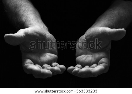 Poor man hands begging with outstretched hands. Hands forming a cup. Poverty and marginalization Concept . Dark background