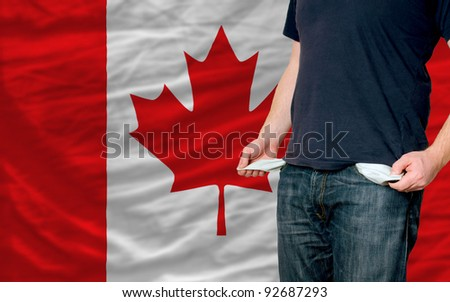 poor man showing empty pockets in front of canada flag - stock photo
