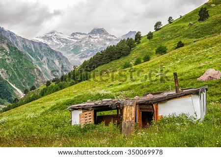 Poor old dilapidated abandoned house of the shepherd on a green meadow in the valley of the mountains, Elbrus region. Doors of house are opened - stock photo