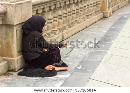 Poor woman begging in the street - stock photo