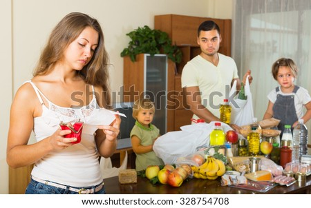Poor young family of four with bags of food at home. Focus on woman  - stock photo