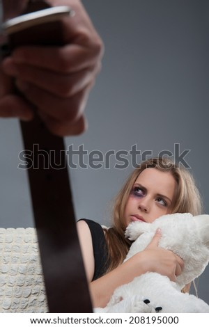 Poor young girl with black eye keeping teddy bear in his hands and looking with the fear at the man holding a girdle - stock photo