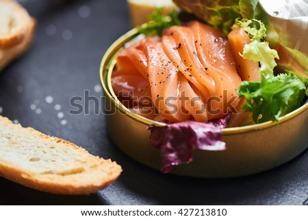 Poorly salted salmon served in a tin and crispy baguette on a stone plaque closeup