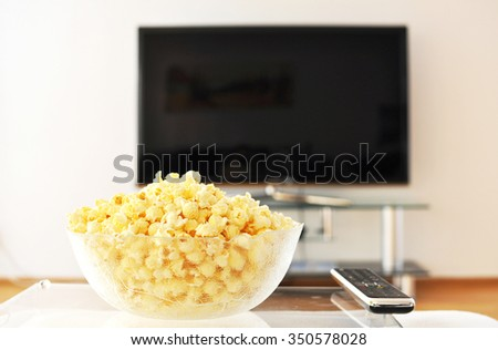 Pop-corn and remote control against TV-set - stock photo