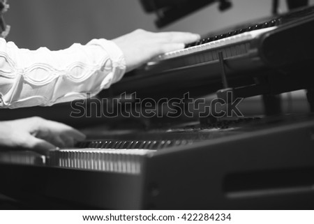 Pop music. Electric piano player plays on two keyboards in one time, black and white photo with selective focus - stock photo