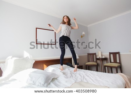 Pop music fan girl jumps on bed while listen to music - stock photo