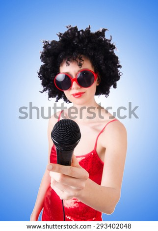 Pop star with mic in red dress against gradient  - stock photo