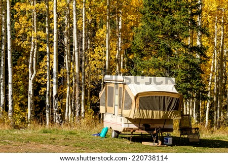 Pop up camper trailer parked in campsite in changing yellow Aspen tree forest on sunny fall morning