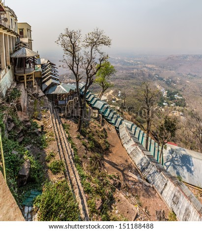 Popa Taungkalat monastery atop an outcrop of Mount Popa volcano, Myanmar. Covered trail for pilgrims - stock photo