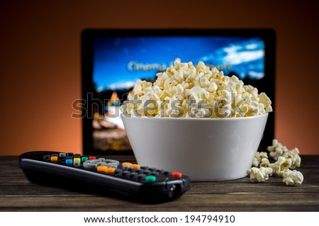 Popcorn and a remote control for the TV background - stock photo