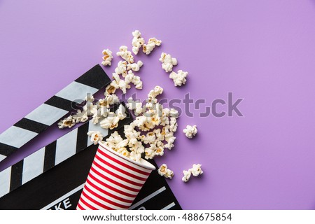 Popcorn and clapperboard on colorful background.