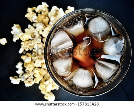 popcorn and cola on the black background - stock photo