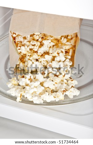 Popcorn cooked in a microwave oven still in the bag. - stock photo