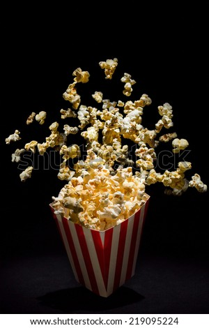 Popcorn exploding from inside the popcorn box - stock photo