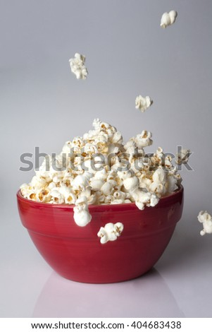 Popcorn falling in red bucket on white background - stock photo