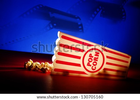 Popcorn for a movie in a popcorn holder and spilling out - stock photo