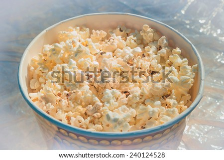 popcorn in a large glass on a table covered with cellophane - stock photo