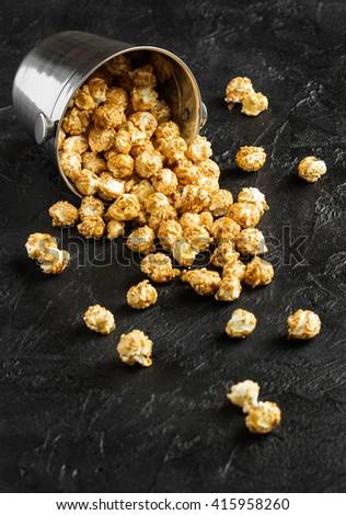 Popcorn in a metal bucket broken up on a dark background - stock photo