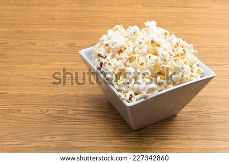 Popcorn in a square shape bowl on wood table - stock photo