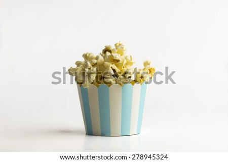 Popcorn in a tiny paper bucket on white background - a concept - stock photo