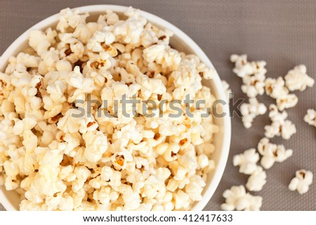 popcorn in a white bowl on a gray background and spilled popcorn