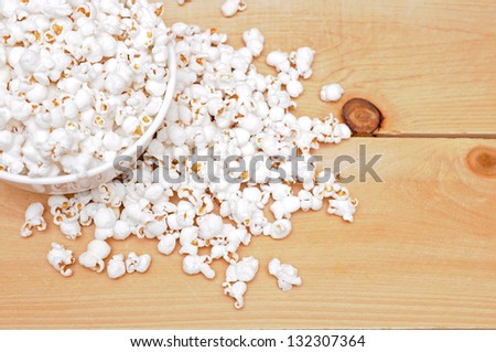 popcorn in bowl on wooden background - stock photo