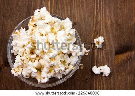 Popcorn in bowl on wooden table seen from above - stock photo