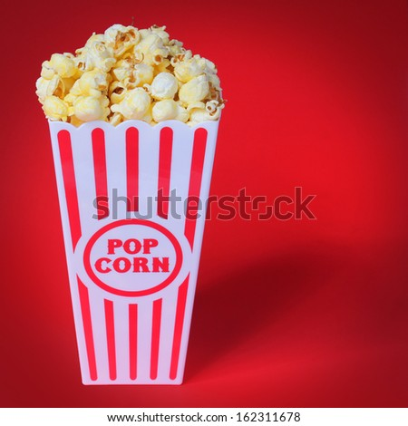 Popcorn in box over red background - stock photo
