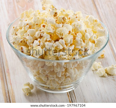 Popcorn in glass bowl on a wooden table. Selective focus - stock photo