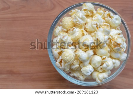 Popcorn in glass bowl on wooden background
