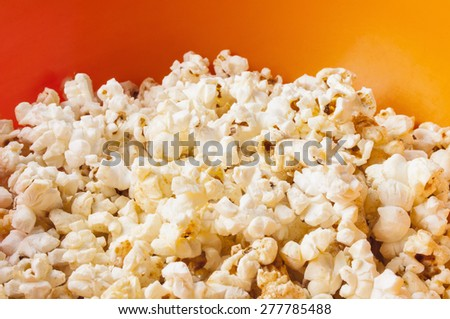 popcorn in orange bright plastic bowl - stock photo