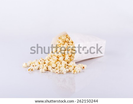 Popcorn in paper bag spread isolated on white background  - stock photo
