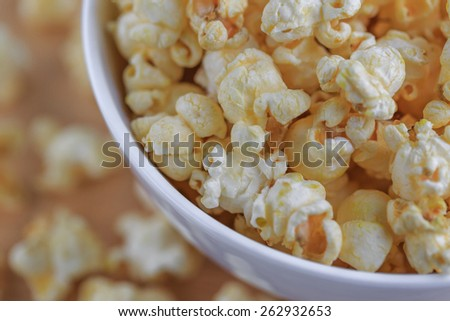 popcorn in white bowl on wood table