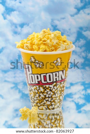 Popcorn on glass with cloud background and container - stock photo