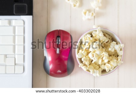 Popcorn with computer on wooden background, shallow focus. - stock photo