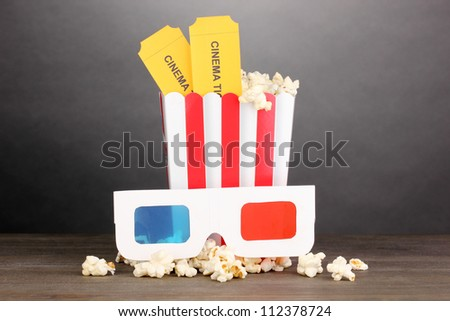 popcorn with glasses and tickets on wooden table on grey background - stock photo
