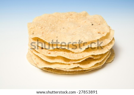 Poppadoms on a blue studio background.