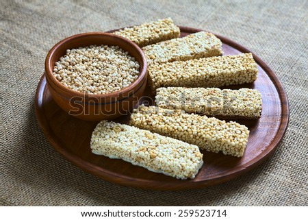 Popped quinoa seeds in bowl with quinoa cereal bars, one with honey the other mixed with amaranth, photographed with natural light (Selective Focus, Focus into the middle of the popped quinoa seeds) - stock photo