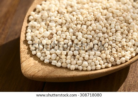 Popped white quinoa (lat. Chenopodium quinoa) cereal on small wooden plate, photographed on wood with natural light (Selective Focus, Focus one third into the quinoa cereal) - stock photo